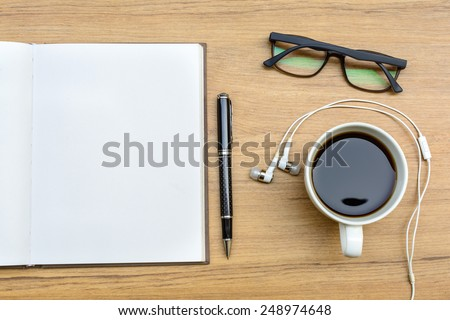 Blank note book with coffee, glasses and headphone - stock photo