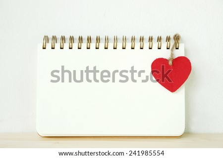Blank note book with red heart on table, valentine's day concept background - stock photo
