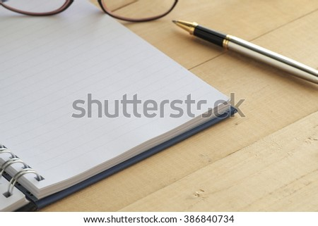 Blank note book with silver pen and glasses on wooden table. - stock photo