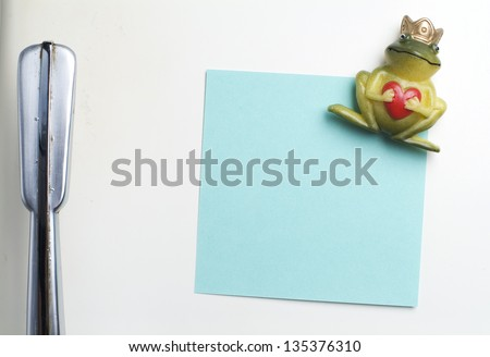 Blank note on fifties fridge-door, close-up of frog with crown holding a heart magnet - stock photo