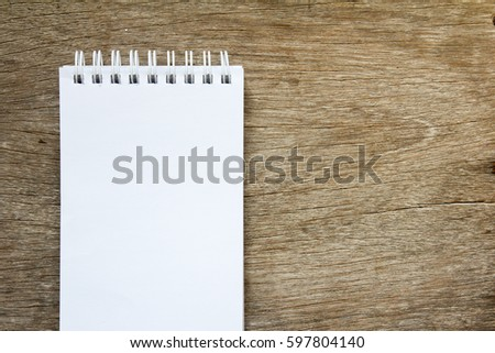 Blank note paper on brown wooden background for memo or remind