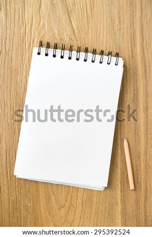Blank note papers and pencil object on a wooden desk in Top view.