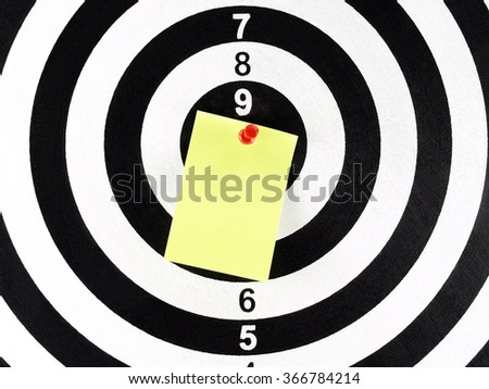 blank note with red pushpin on target center of dartboard - stock photo