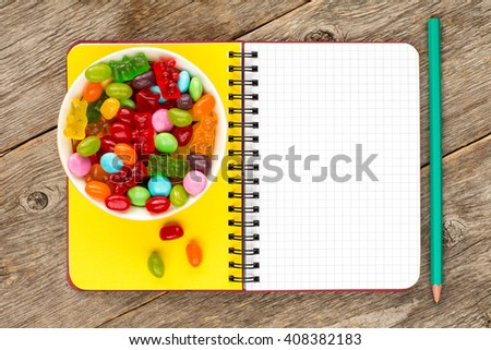 Blank notebook and bowl with mixed candies