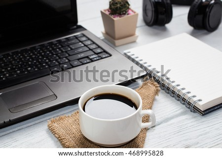 Blank notebook and cup coffee,laptop on table background copy space / selective focus