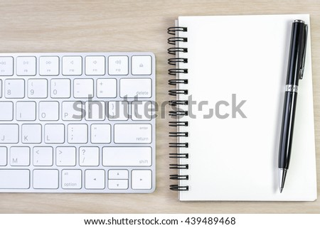 blank notebook and pen with keyboard on wooden table, writing concept - stock photo