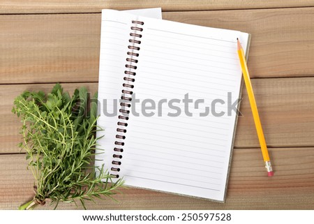 Blank notebook and pencil with a bunch of herbs on wooden board