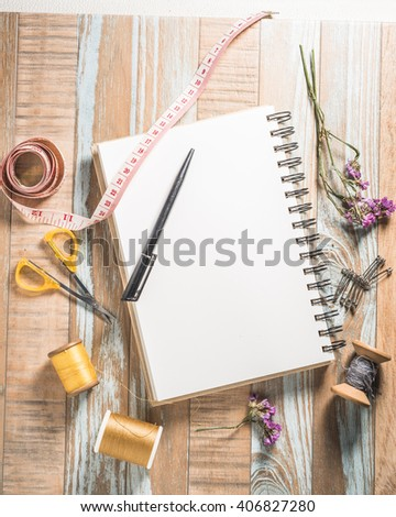 Blank notebook and sewing kit on wooden textured background, copy-space. - stock photo