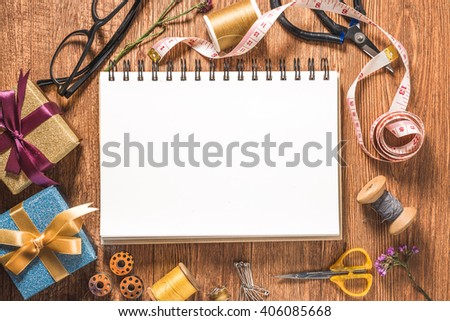 Blank notebook and Sewing tools on wooden textured background, copy-space. - stock photo