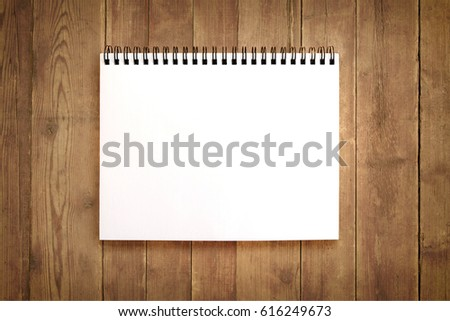 Blank notebook on brown wooden background