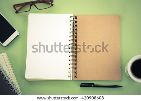 blank notebook on green table top view