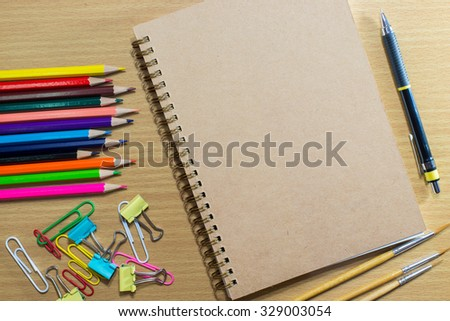 Blank notebook on school and frame of colorful school supplies  - stock photo