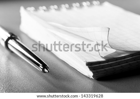 blank notebook on table with pen. Blue toned, shallow dof