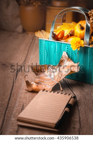 Blank notebook  on wooden table on the wintage kitchen with Autumn decorations. Shallow DOF, focus on the autumn leaf. This image is toned - stock photo