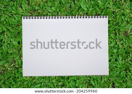 blank notebook recycle paper open two page with copy space area for multipurpose use open on green grass field - stock photo
