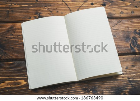 Blank notebook up close on a rustic wooden background - stock photo