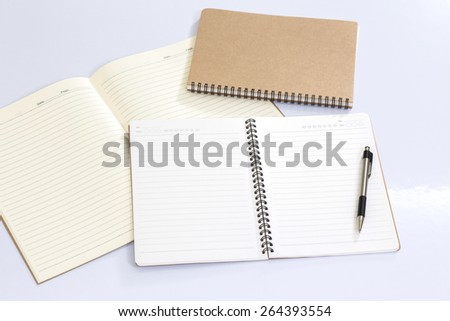 Blank notebook with a pen on white table - stock photo