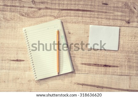 Blank notebook with a pencil on a wooden table business concept (black vintage).