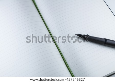 Blank notebook with fountain pen   in composition of black and white