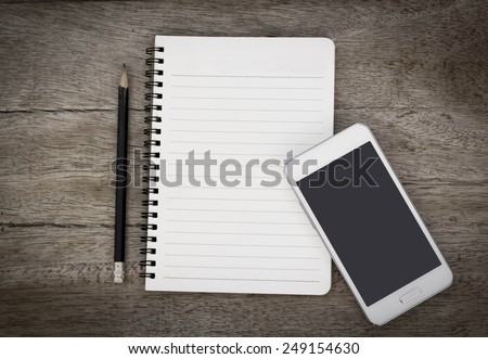 Blank notebook with mobile smart phone on wooden table. - stock photo