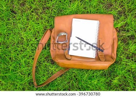 Blank notebook with pen and brown bag on Green Grass background. - stock photo