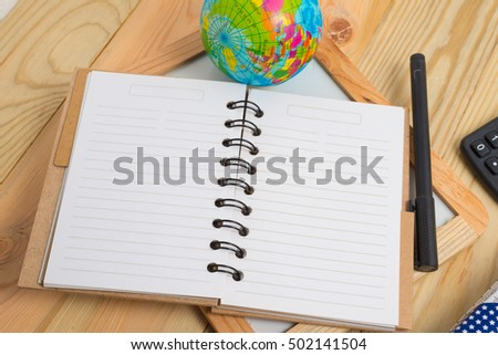 blank notebook with pen and calculator on wooden table, business concept