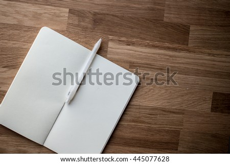 blank notebook with pen and pencil on wooden table - stock photo