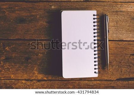 blank notebook with pen on a old wooden table - stock photo