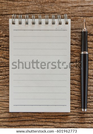 Blank notebook with pen on wooden table, business concept