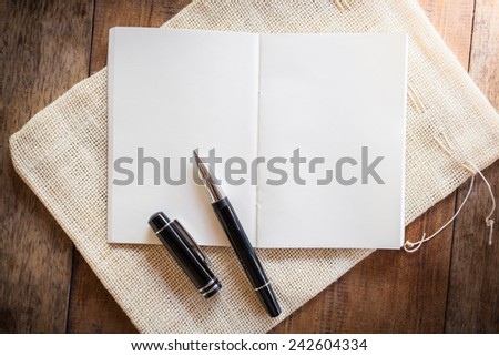 Blank notebook with pen on wooden table. The view from the top - stock photo
