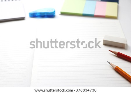 Blank notebook with pencil, red pencil, pen, tag paper, notepad, correction tape, and eraser on white background. - stock photo