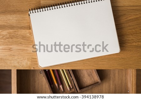 Blank notebook with pencils in box on the desk. Overhead view - stock photo