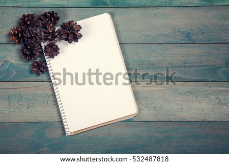 Blank notebook with pine cones on wooden background
