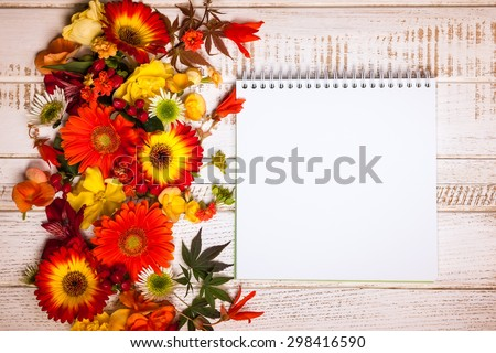 Blank notepad and autumnal flowers  on vintage wooden background. Top view with copy space - stock photo