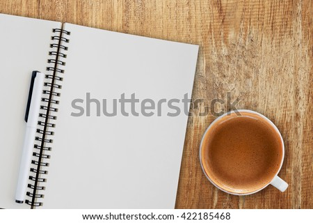 Blank notepad and coffee cup on wooden table. - stock photo