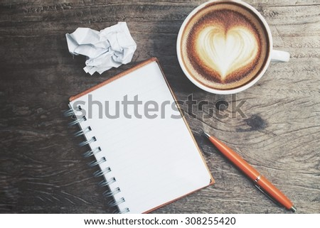 Blank notepad and pen with latte art coffee on office table - stock photo