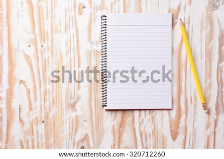 Blank notepad and pencil on wood table with copy space