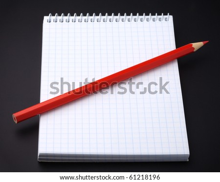 Blank notepad and red pencil as an organizer on black background - stock photo