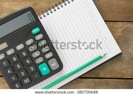 Blank notepad, calculator and pen laying on it on office wooden table - stock photo