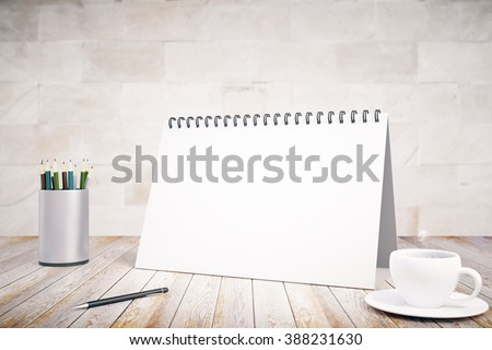 Blank notepad cover, cup of coffee and pen on wooden table, mock up - stock photo