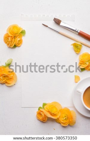 Blank notepad, flowers, brushes and cup of coffee over white wooden background. Top view with copy space, selective focus - stock photo