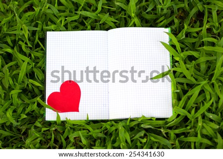 Blank notepad for copy space on green grass. Love to write  - stock photo
