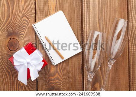 Blank notepad for copy space, valentines day gift box and two champagne glasses over wooden background - stock photo