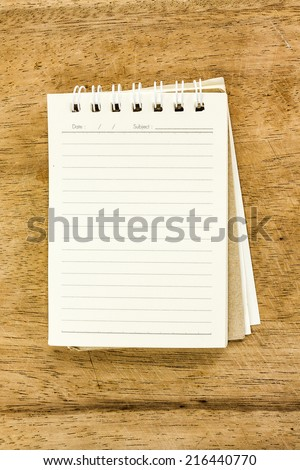 Blank notepad on wooden desk - stock photo