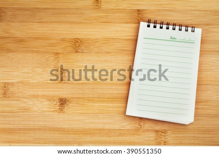 Blank notepad on wooden table , overhead shot or Top view