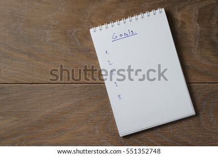 blank notepad on wooden table with word goals, space for your text
