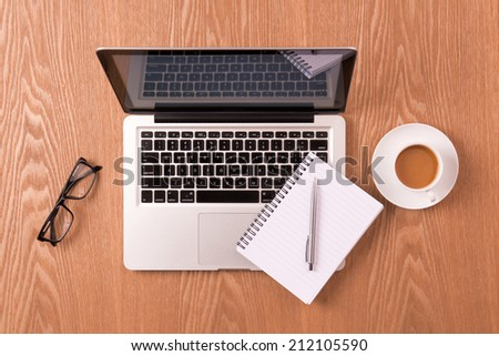 Blank notepad over laptop and coffee cup on wooden table. A workplace office - stock photo