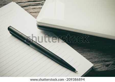 Blank notepad over laptop wooden table
