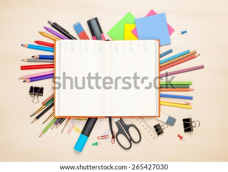 Blank notepad over school and office supplies on office table. Top view with copy space - stock photo