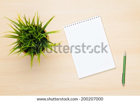Blank notepad, pen and flower on wooden table. View from above - stock photo